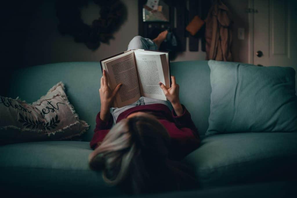Dziewczyna czytająca książkę na kanapie